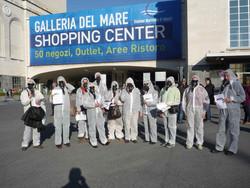 """Attivisti del """"Comitato Pace, Disarmo e Smilitarizzazione del Territorio - Campania"""" al porto di Napoli con tute bianche e maschere antigas si schierano davanti alla """"Galleria del Mare"""""""